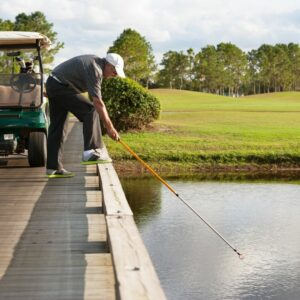 Golfer fishing out ball with golf ball retriever